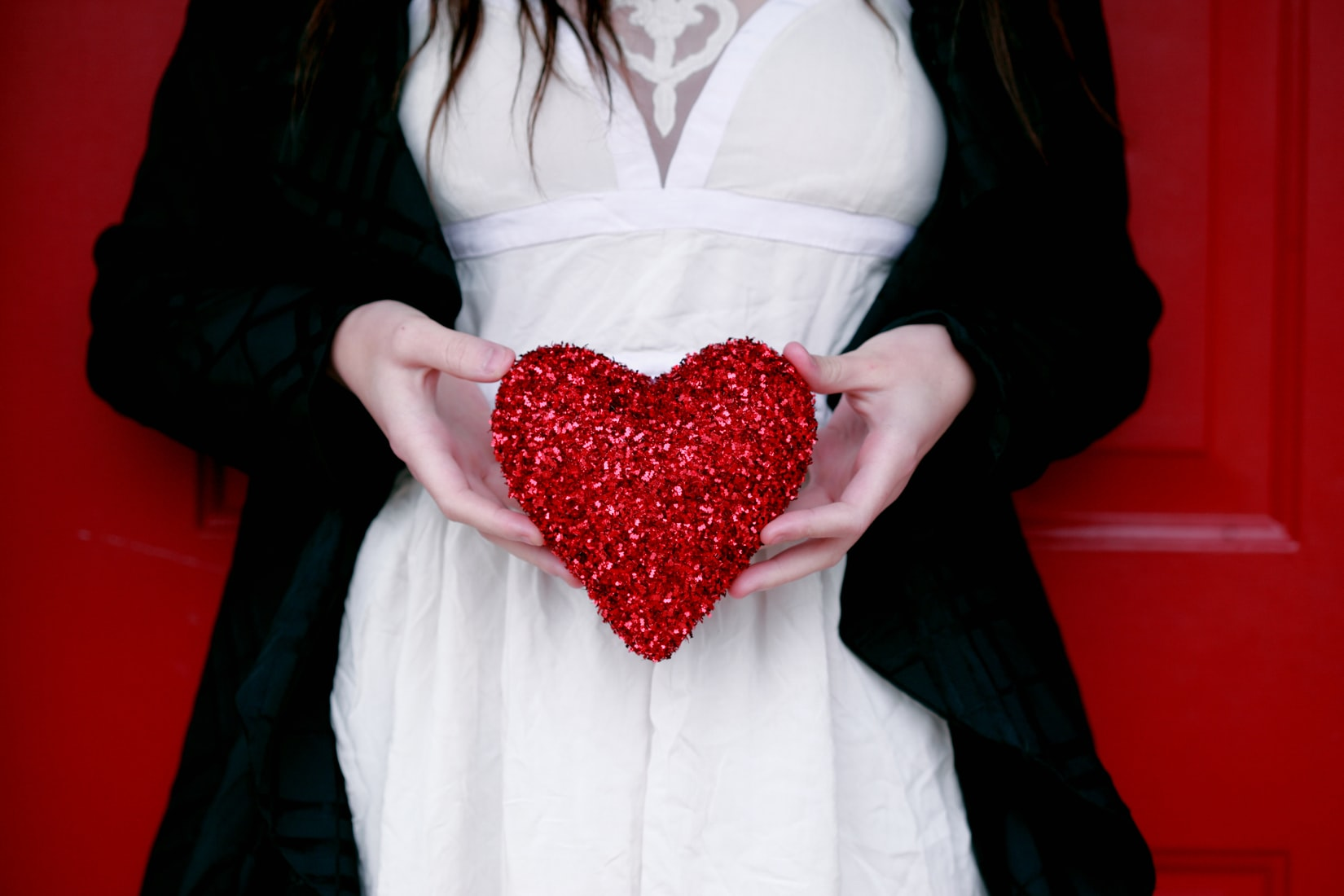 White woman holding red heart pillow in front of red door