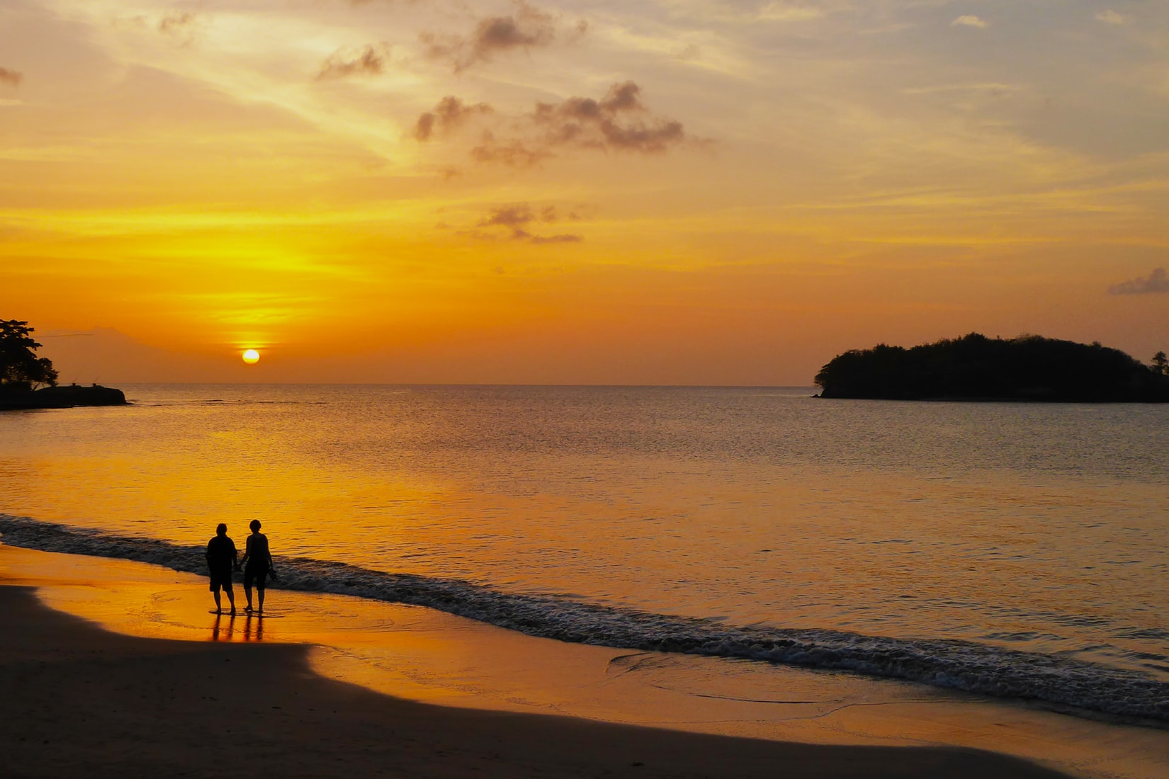 Two people in love on beach during sunset