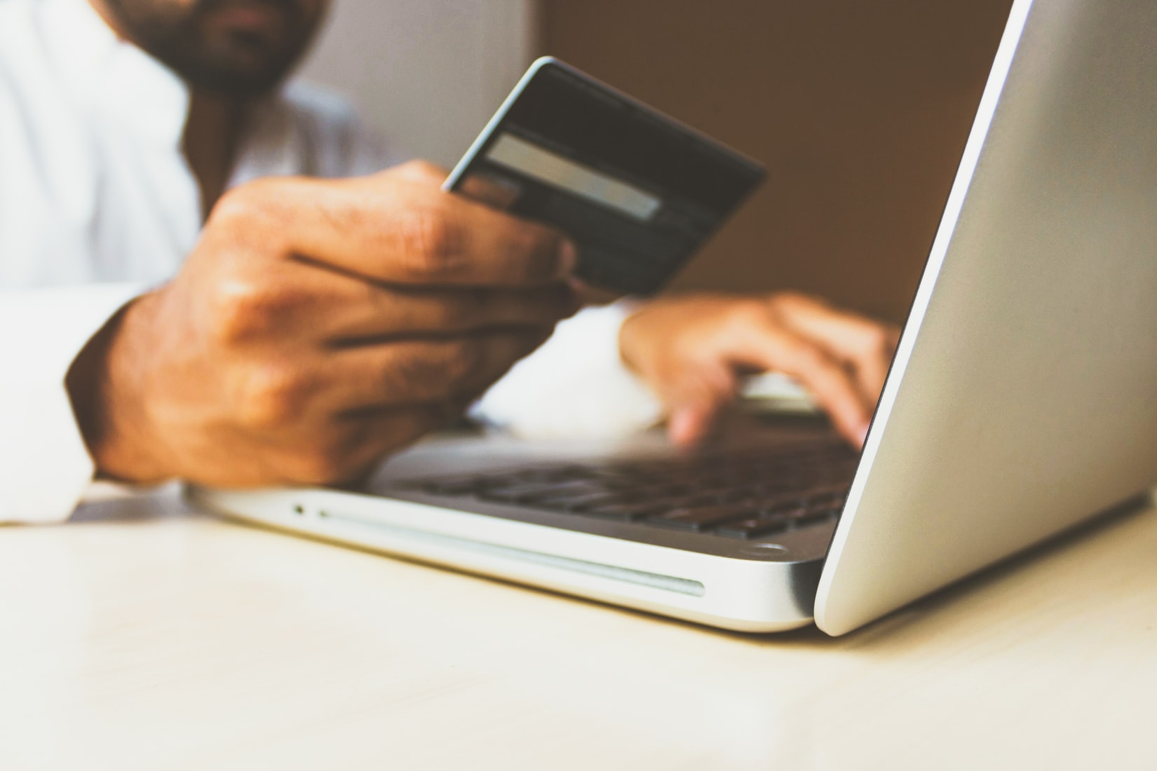 Greedy man holding debit card while typing on laptop