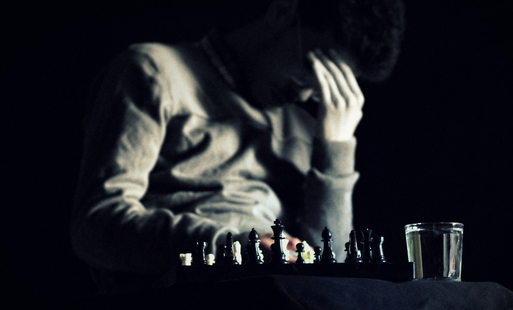 Depressed man with hand on face sitting in front of chessboard