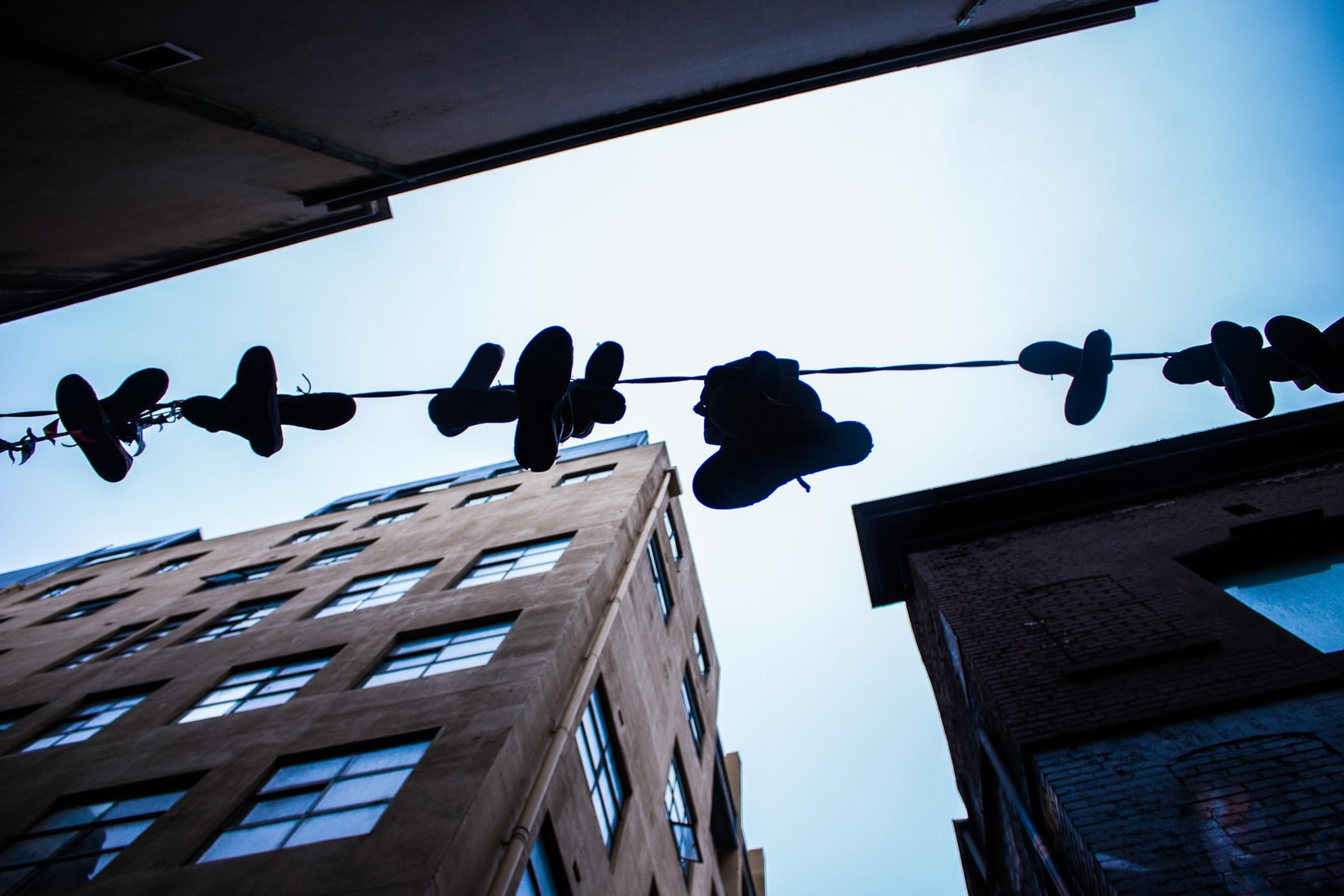 Low-angle photo of hanged shoes on wire next to buildings during daytime