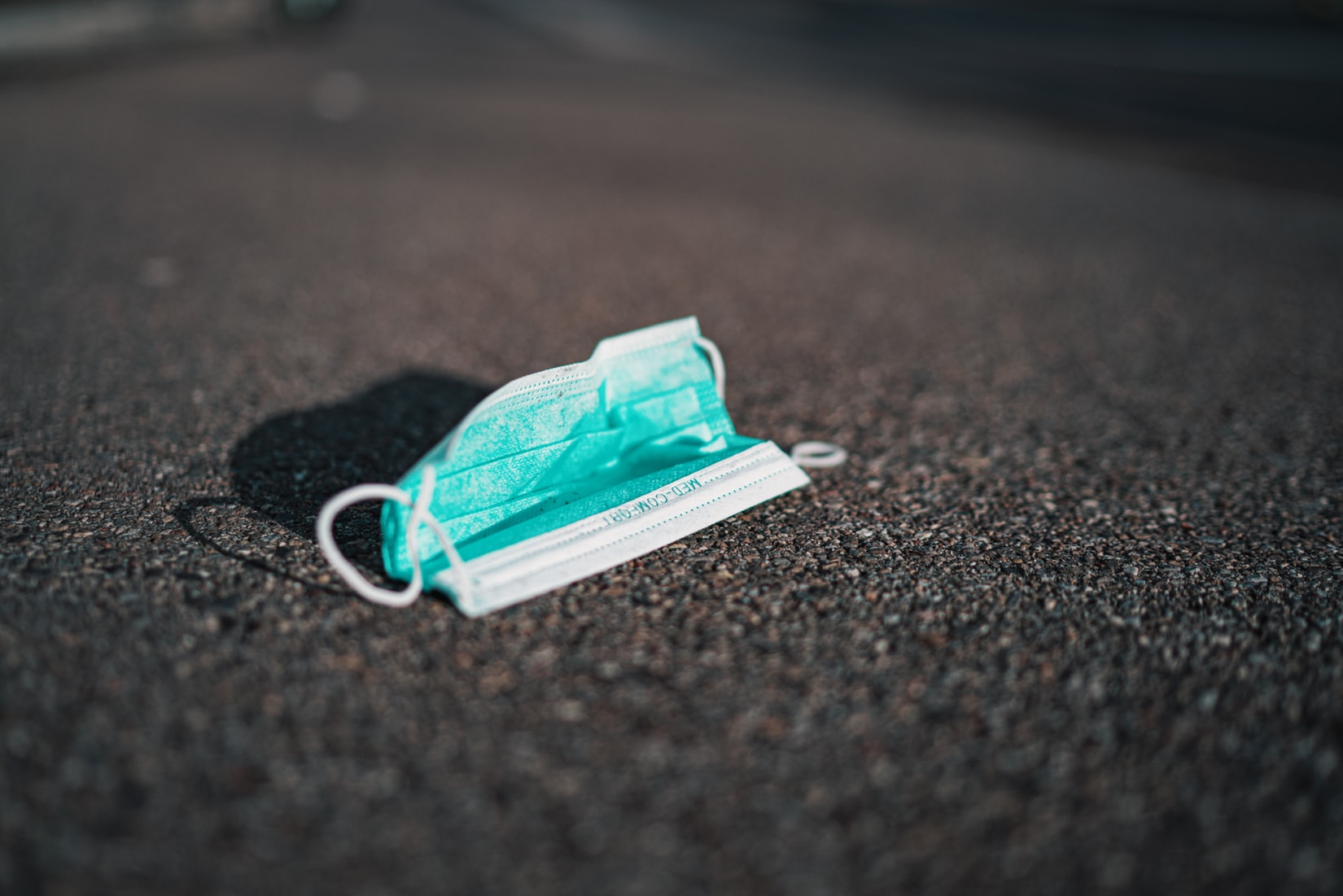 Turquoise medical face mask on ground