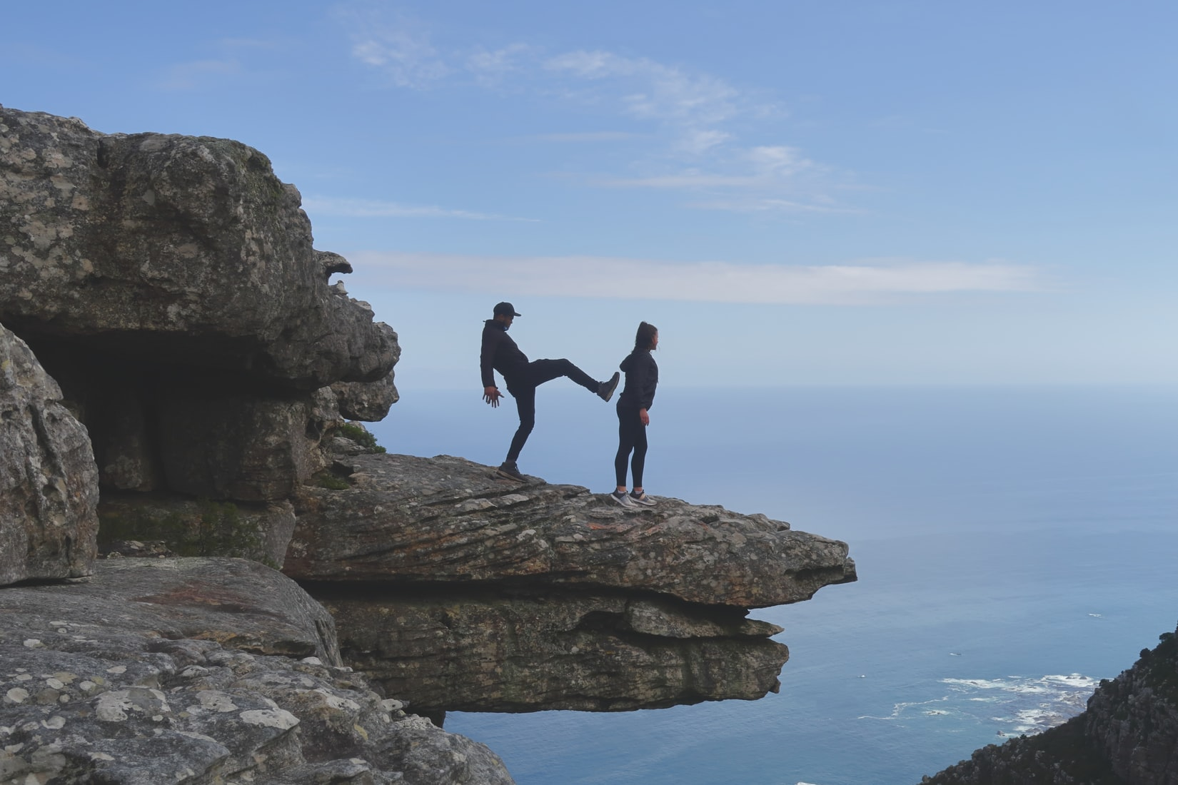 Man about to kick woman standing on cliff near ocean