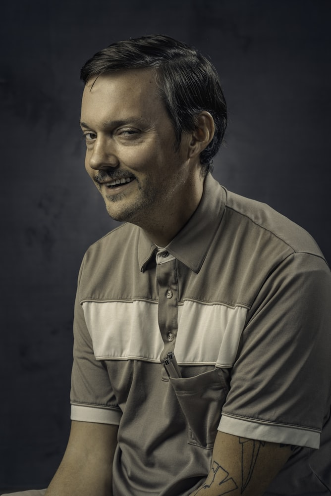 Psychotic man smiling and wearing gray polo shirt with tattoo on left arm