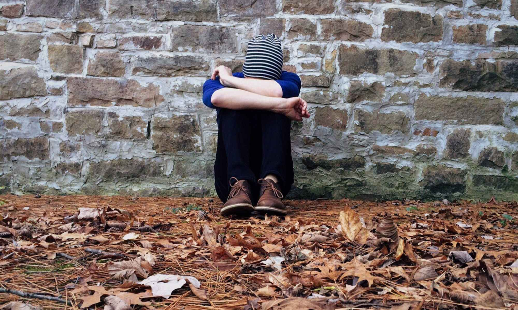 Young depressed person sitting on ground with leaves by stone wall with head down