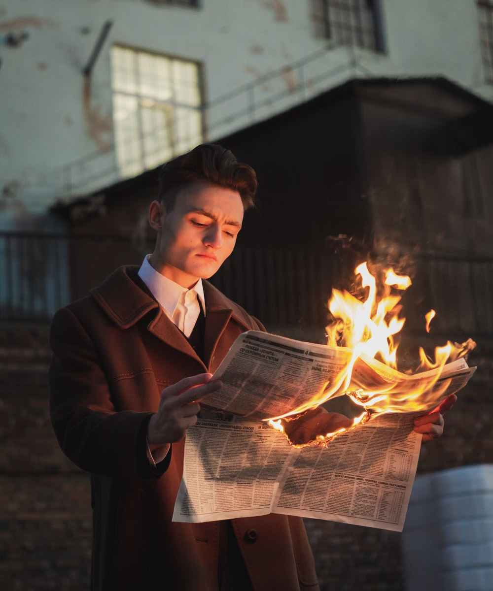 Sociopathic man reading newspaper on fire standing in front of old building