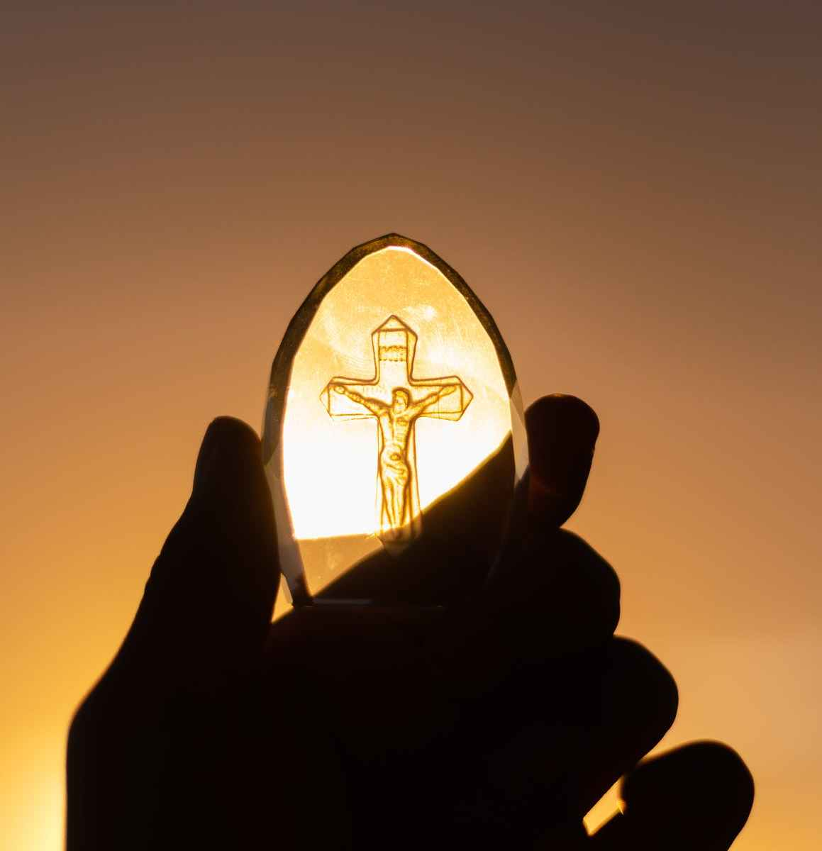Person's hand holding glass of Jesus Christ on cross