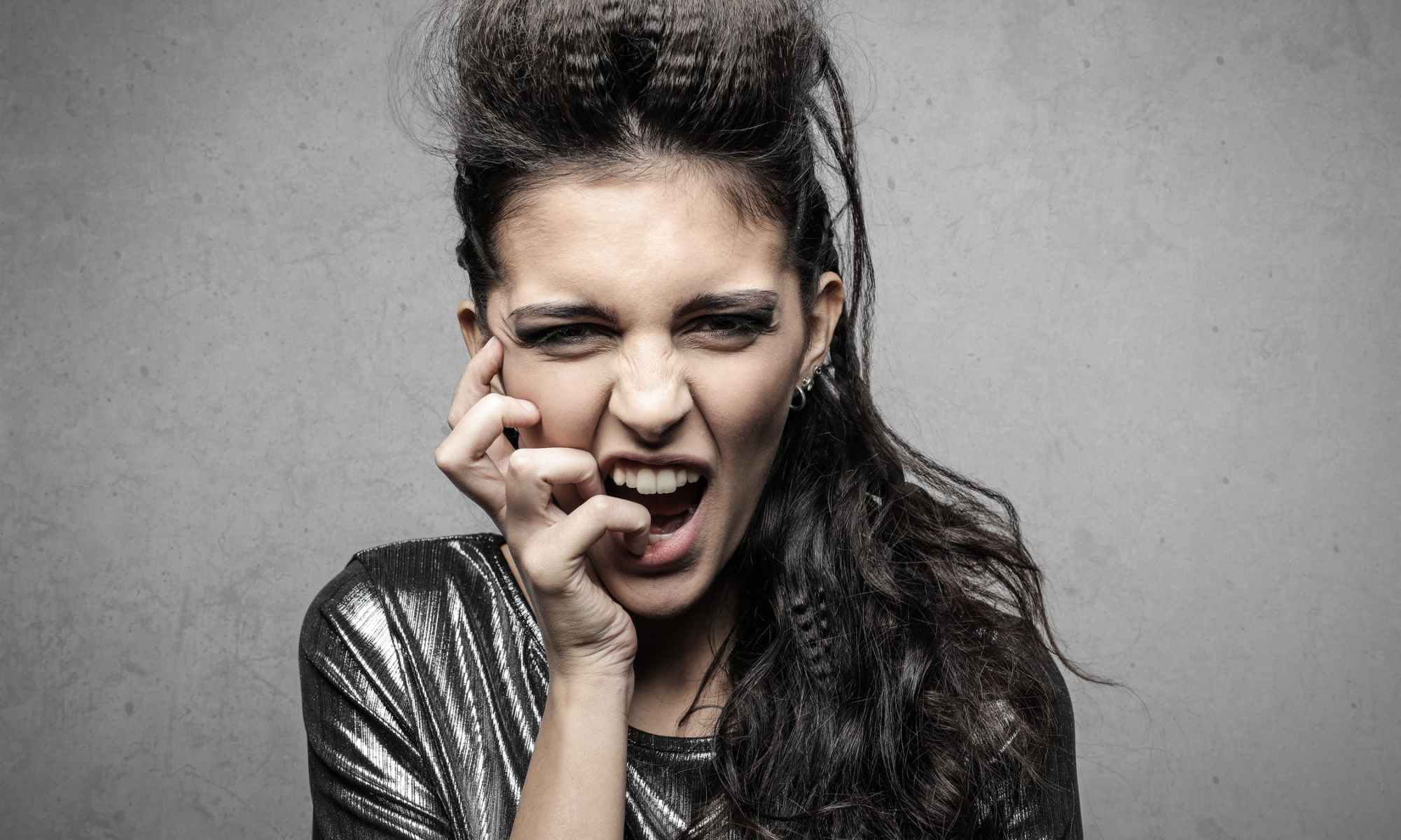 Manic woman with long dark hair with hand on face with open mouth