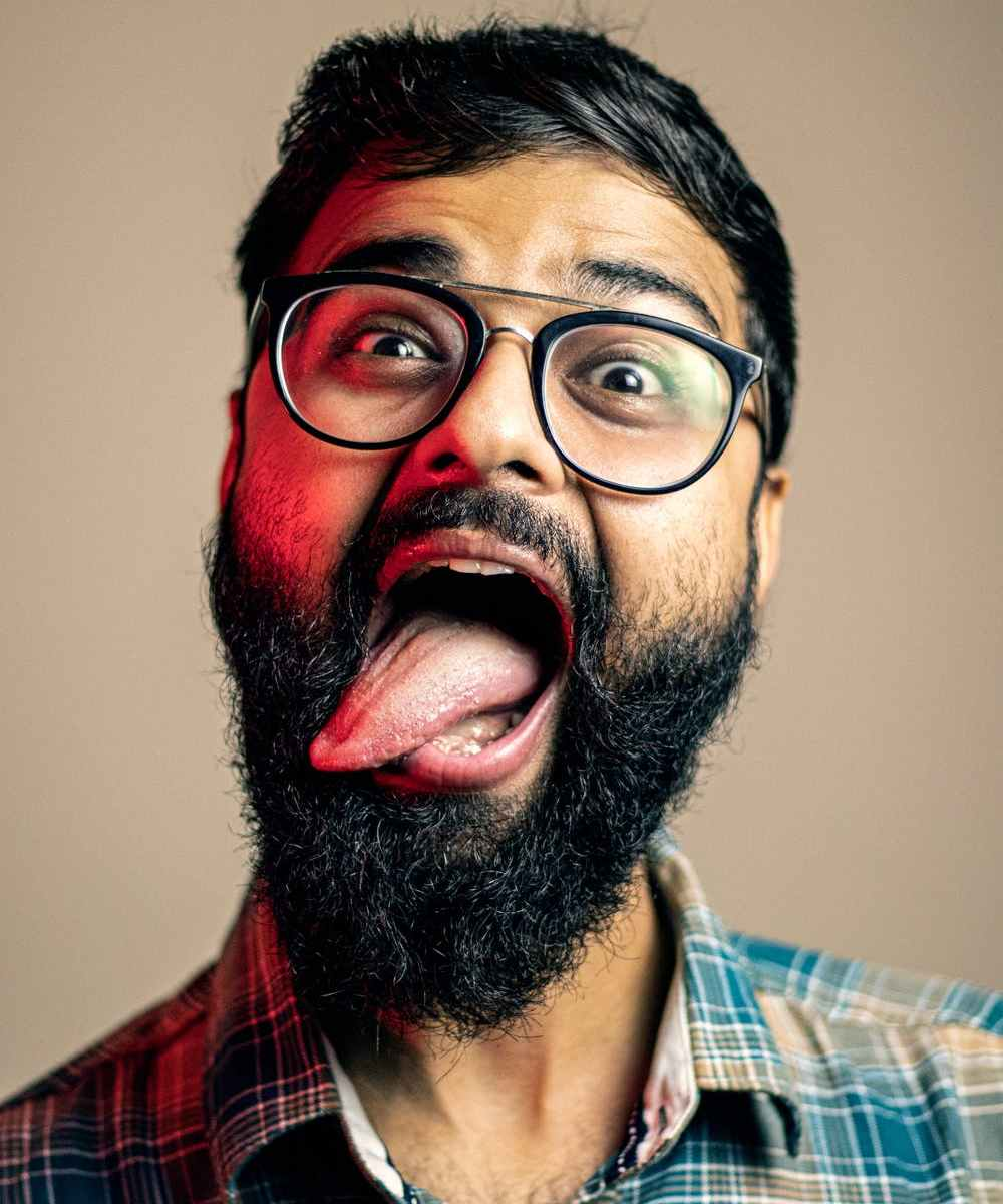 Psychotic Indian man wearing glasses sticking tongue out