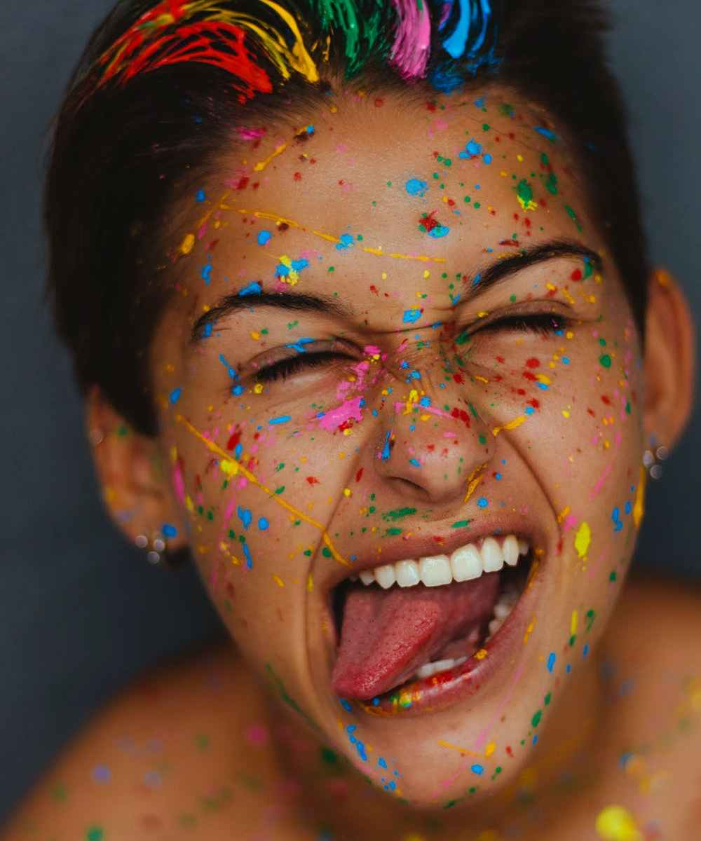 White woman's face with color splatters on hair and face