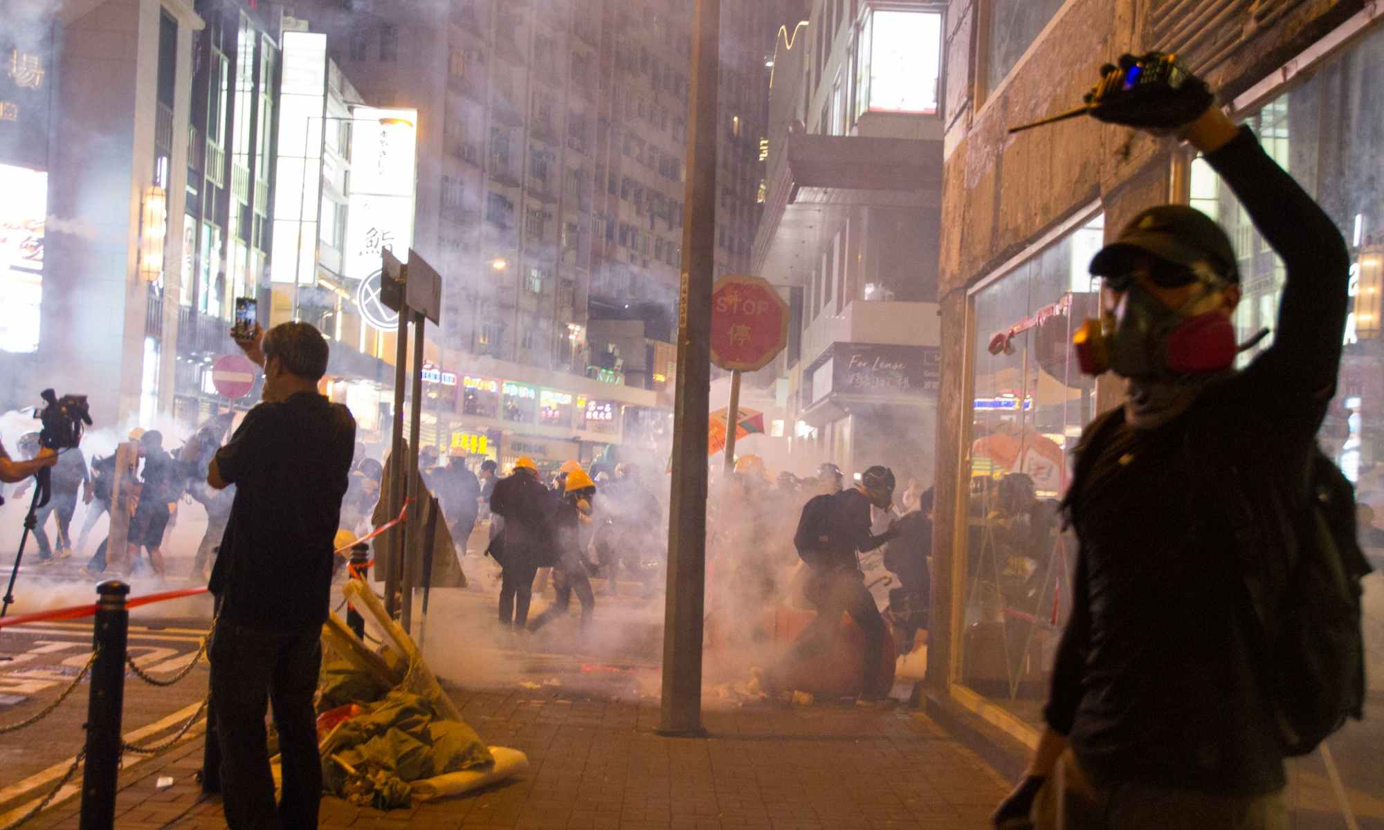 People wearing gas masks in city streets rioting