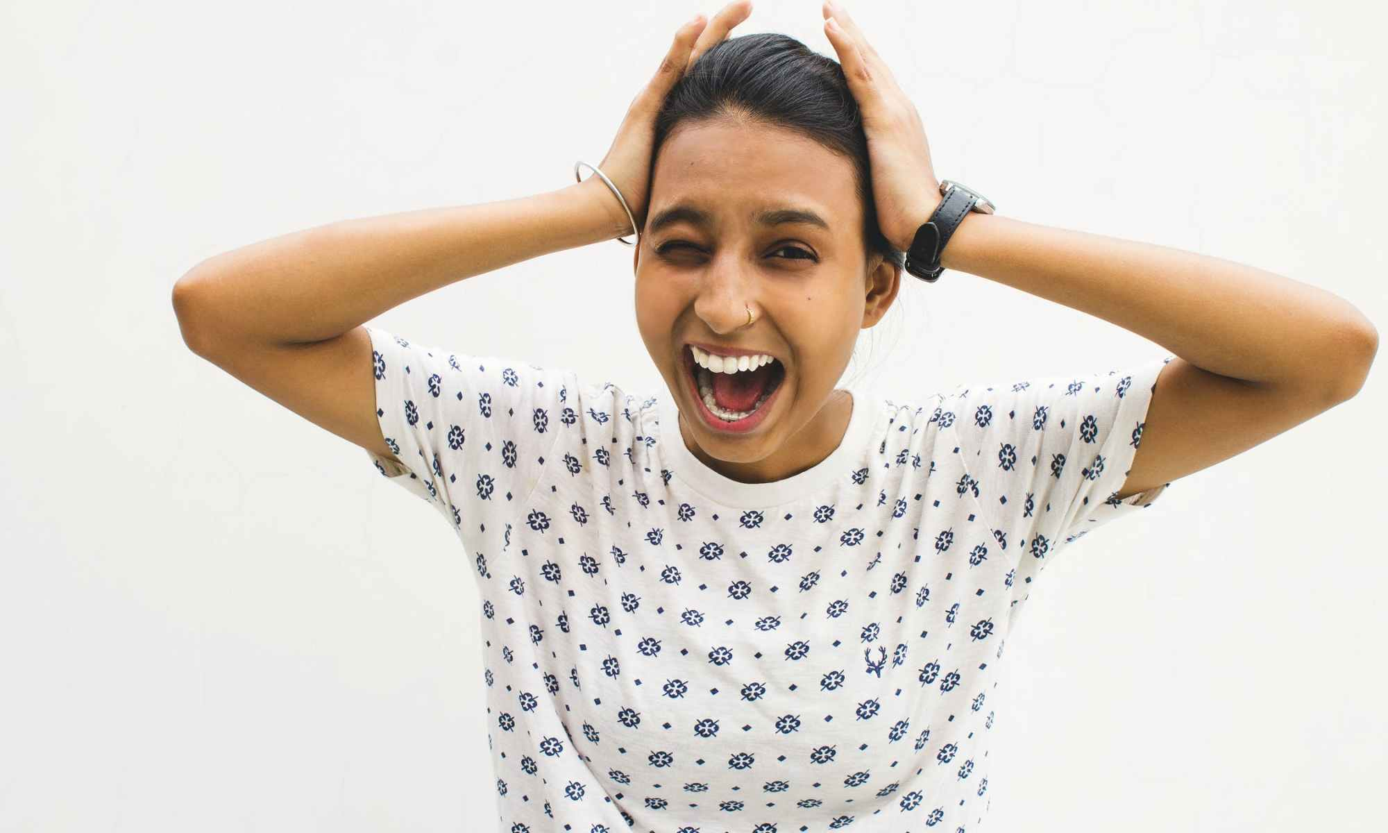 Excited brown manic woman holding hands on head