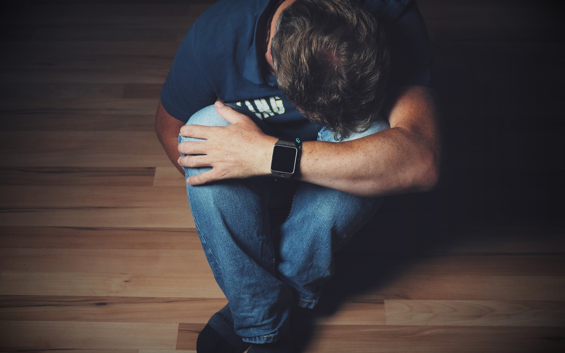 Depressed man sitting on wooden floor with head down on lap