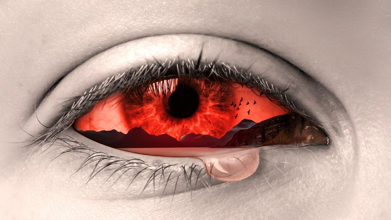 Red human eye with pink liquid dripping out