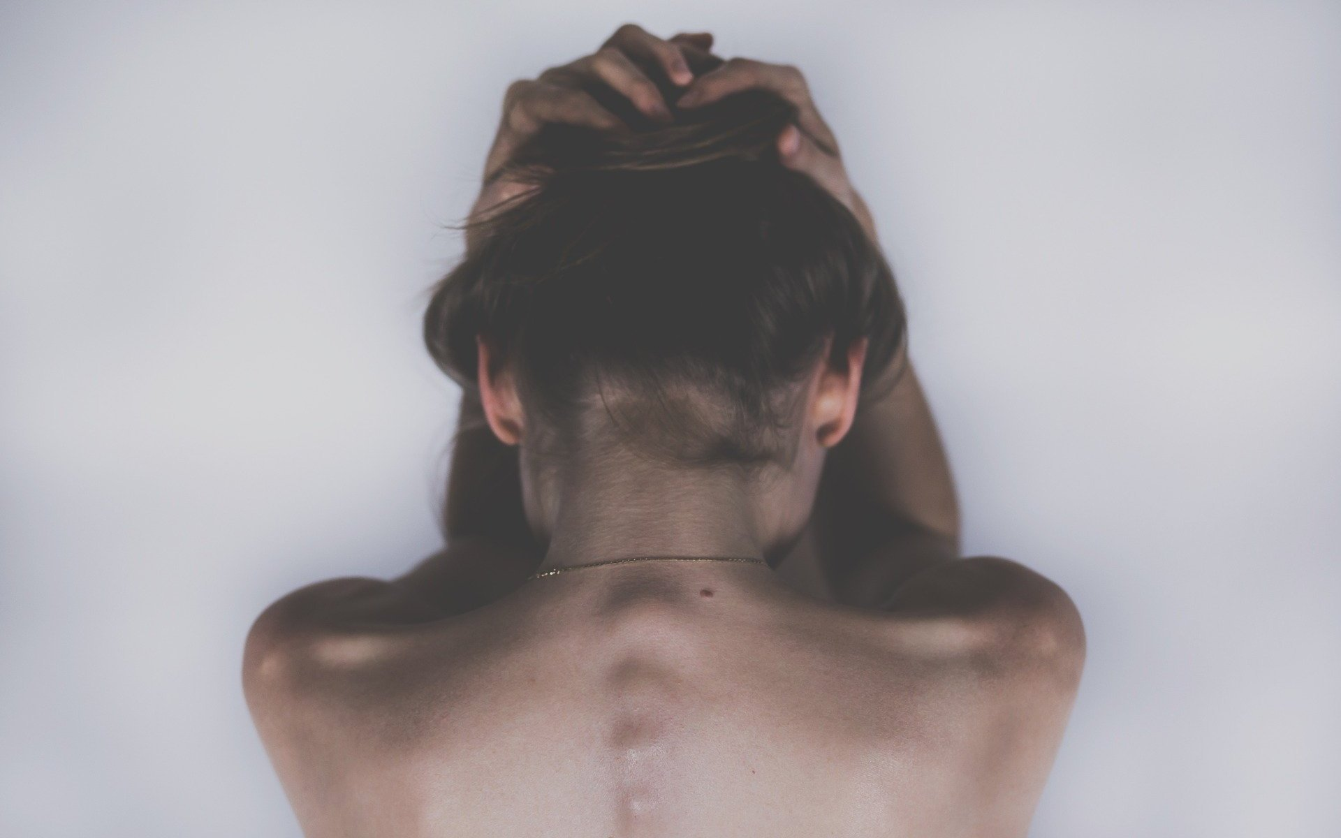 Topless sad woman holding head down with both hands