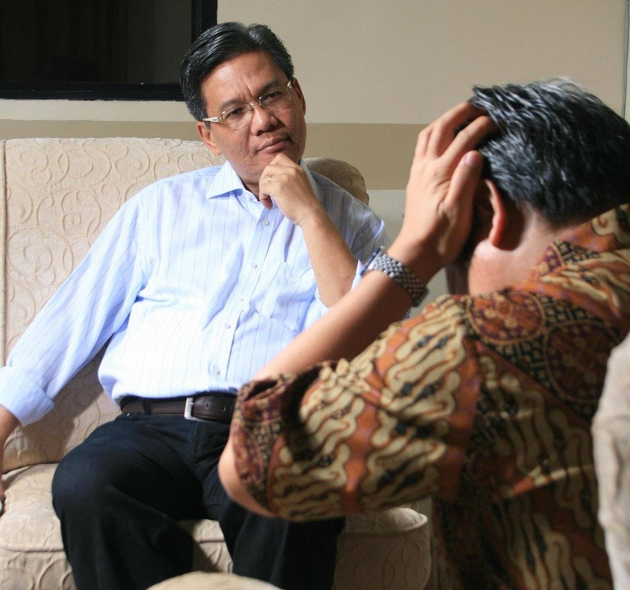 Male psychiatrist sitting on couch talking to patient with hands on head