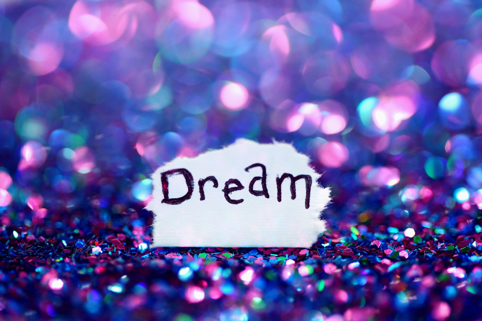 A simple message to dream with shimmery purple and pink glitter bokeh