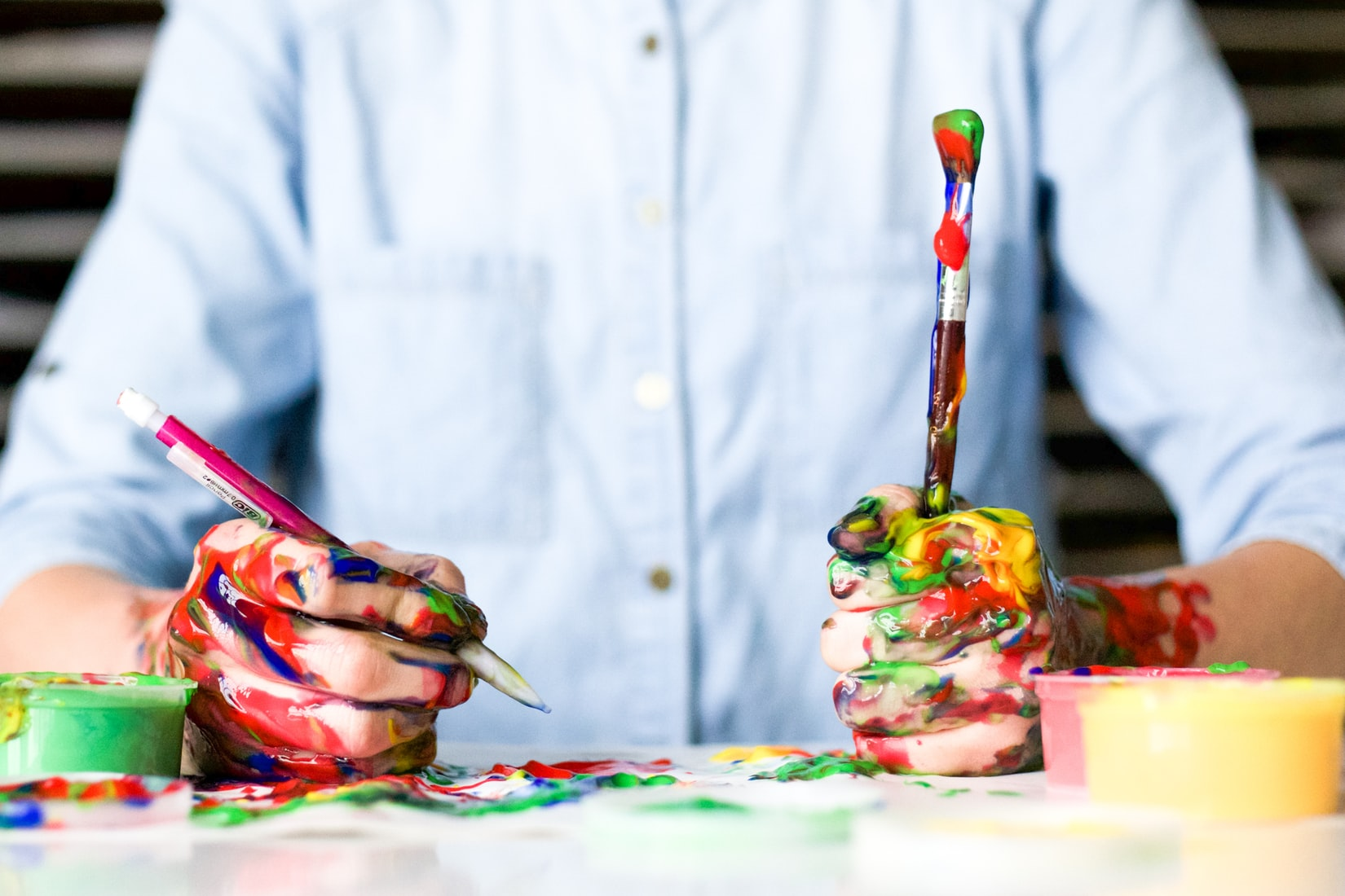 Person holding paintbrush covered in paint