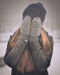 Insecure woman wearing winter clothes and covering face with gloves