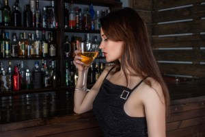 White woman holding cocktail drink next to bar