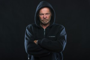 Negative people's characteristics: angry white man wearing hoodie with folded arms