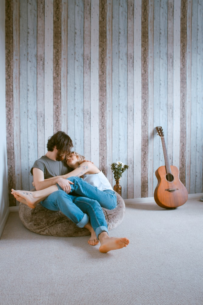 White man and woman in love sitting on gray beanbag