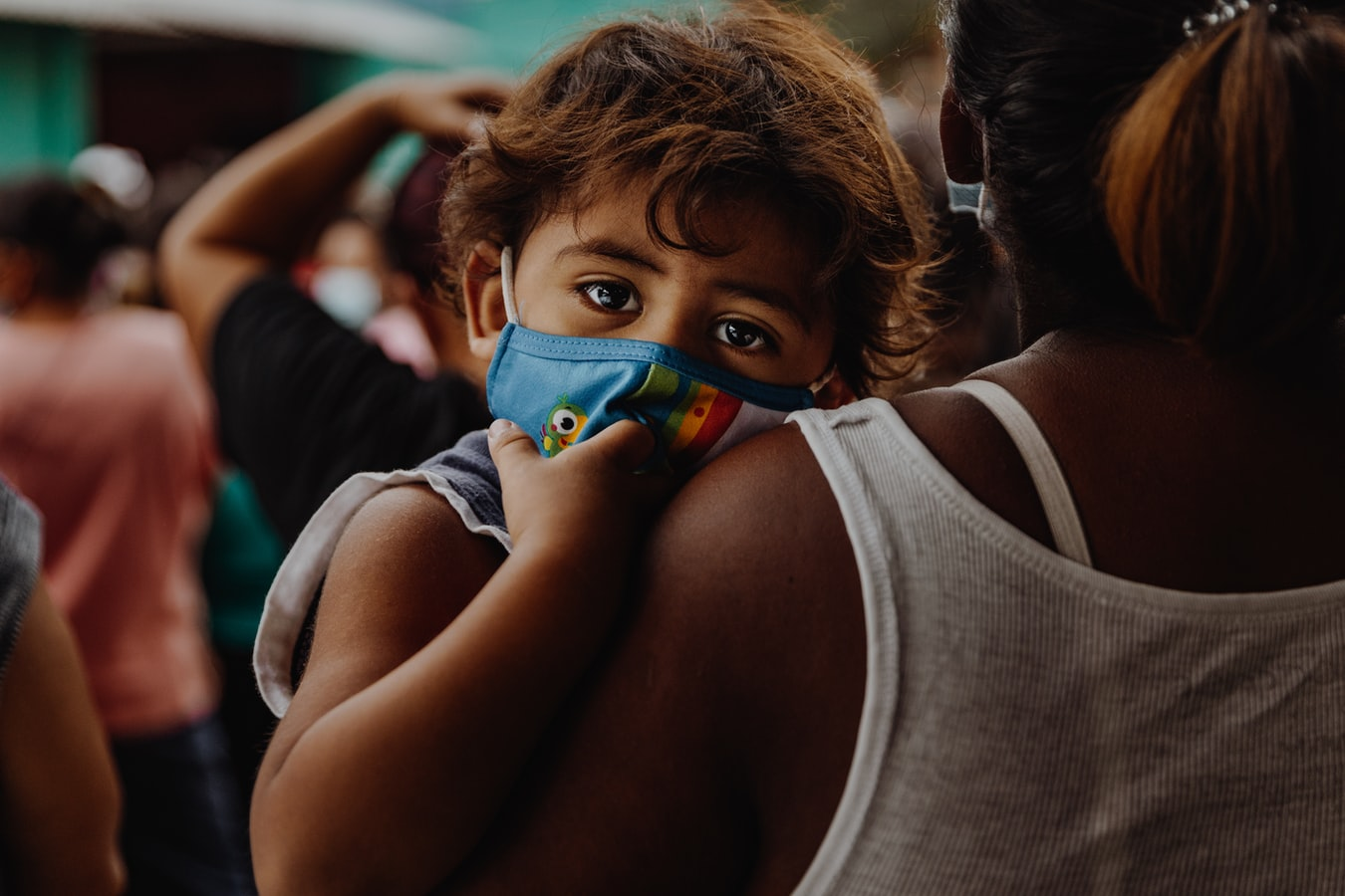 Black woman in white tank top holding sad child with mask on face