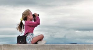 cute-young-girl-with-blonde-hair-looking-through-binoculars-taking-in-the-view-or-looking-into-the_t20_roxwVz