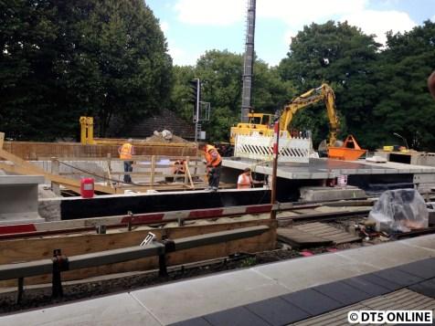 Es finden hier Arbeit im Aufgang statt. Die beiden Bauarbeiter hinter der Absperrung müssten im Fahrtreppenschacht stehen. Am rechten Bildrand ist die Bahnsteigverlängerung zu sehen, welche schon weit fortgeschritten ist.