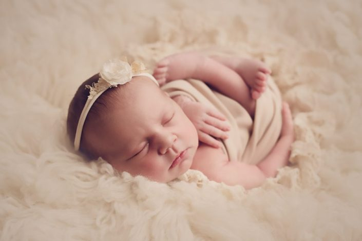 newborn baby photographed on cream backdrop