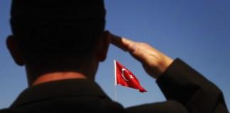 Ein türkischer Soldat salutiert vor einer türkischen Flagge.