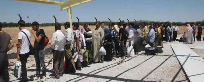 Menschen stehen Schlange an der türkisch-syrischen Grenze