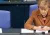 Bundeskanzlerin Angela Merkel (CDU) sitzt am 22.11.2012 im Reichstag in Berlin während einer Sitzung des Bundestags auf ihrem Platz und schaut auf ihr Mobiltelefon. Das Handy von Merkel ist möglicherweise von US-Geheimdiensten überwacht worden.