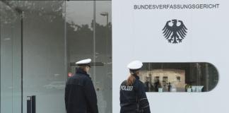 Zwei Polizisten laufen am 03.12.2013 in Karlsruhe (Baden-Württemberg) vor dem Eingang zum Bundesverfassungsgericht entlang. Nach monatelanger Vorbereitung wollen die Länder an diesem Dienstag einen neuen Verbotsantrag gegen die rechtsextreme NPD beim Bundesverfassungsgericht in Karlsruhe einreichen.