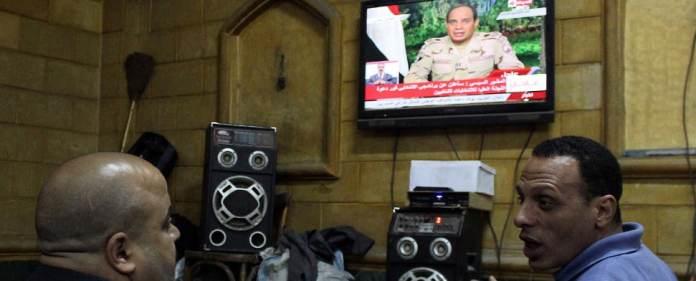 Zwei Männer in Kairo lauschen einer Fernsehansprache von al-Sisi.