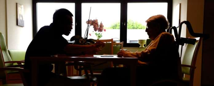 Der Azubi zum Altenpfleger, der Vietnamese Long Pham Dinh, unterhält sich am 19.09.2013 im Pflegeheim Eilenriedestift in Hannover (Niedersachsen) mit einer Seniorin.