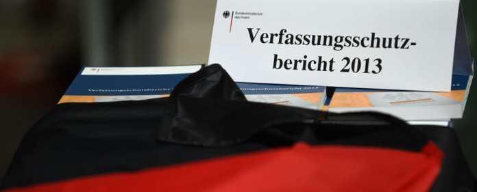 Ausgaben des Verfassungsschutzberichts 2013 liegen am 18.06.2014 zu Beginn einer Pressekonferenz in Berlin unter einer Deutschlandflagge. Der Bericht wurde vom Bundesinnenminister und dem Verfassungsschutzpräsidenten vorgestellt.
