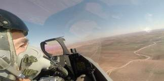 Das Innere eines Kampfjet-Cockpits über einer Wüstenlandschaft.
