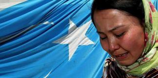 Eine uigurische Frau weint vor der blauen Flagge ihres Volkes.
