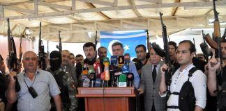 Bewaffnete Turkmenen stehen um ein Rednerpult ihres Anführers: Arshad al-Salihi, Vorsitzender der Turkmenenfront des Irak (Irak Türkmen Cephesi; kurz ITC)