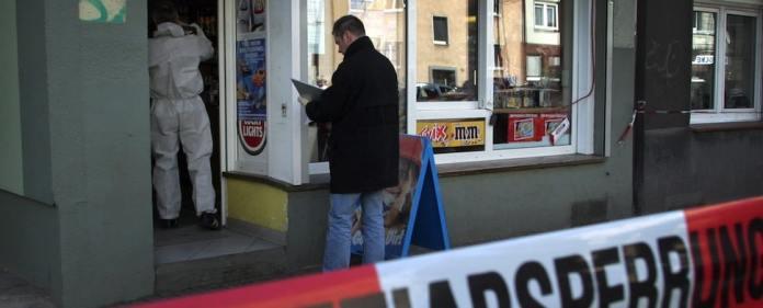 Polizeibeamte untersuchen nach einem Mord in Dortmund einen Kiosk auf Spuren