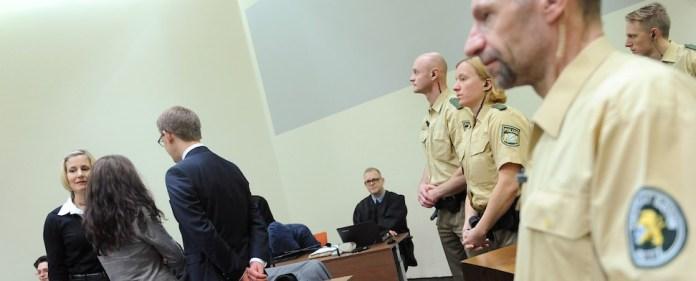 Die Angeklagte Beate Zschäpe steht während des NSU Prozess mit dem Rücken zur Polizei und der Kamera.
