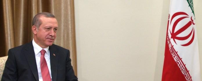 Erdogan sitzt lächelnd neben der Flagge der Islamischen Republik Iran.