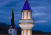 Ein Minarett ist vor einem Kirchturm zu sehen.