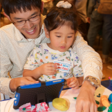 Man holding toddler looking at a computer