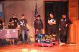 Boys standing next to their robot