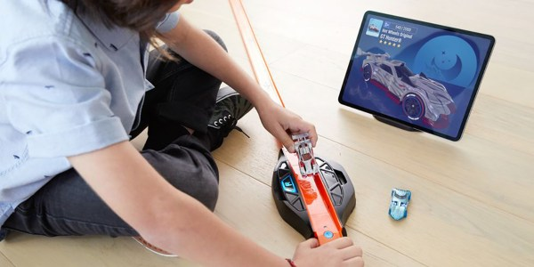kid playing with Hot Wheels and iPad