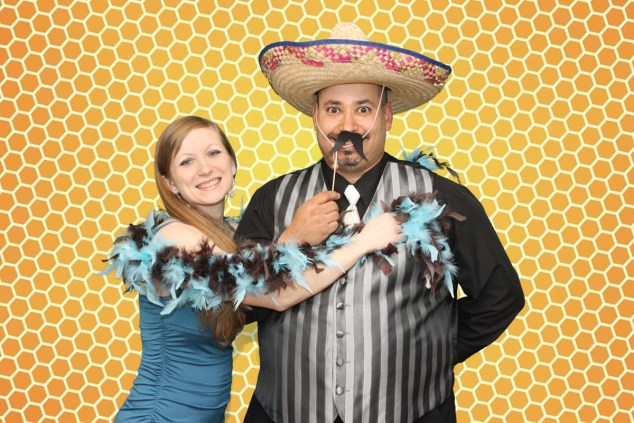 a lady and a man with a sombero standing in front of a green screen background that has been replaced with what looks like a bee hive background