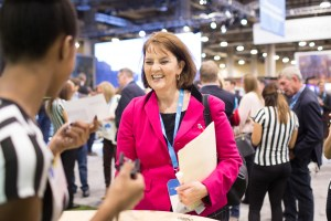 a lady receiving promotional material at a corporate event