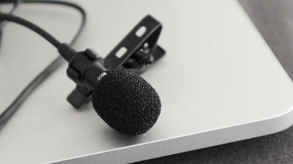 A macro image of a lapel microphone sitting on the edge of a video production laptop